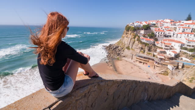 Vrouwelijke toeristische met uitzicht op een dorp op de kliffen aan de Oceaan