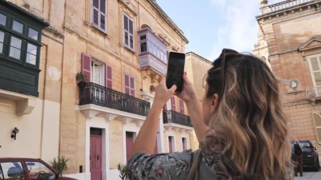 vídeos y material grabado en eventos de stock de turista femenino - viajero en solitario que explora europa - photographing
