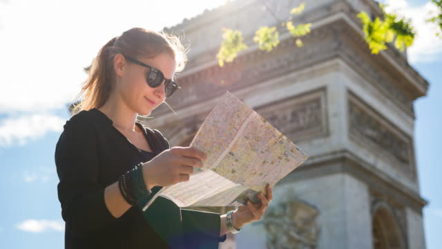 Female tourist standing in front of Arch of Triumph in Paris and looking at city map
