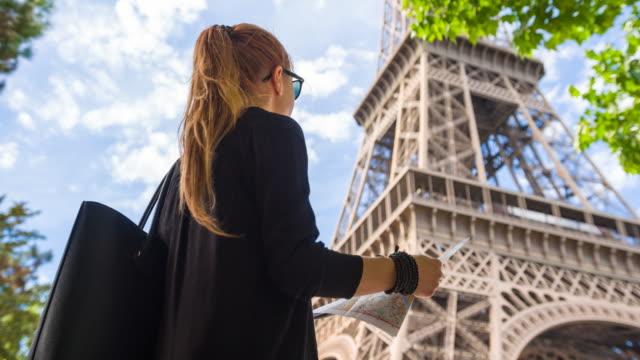 weibliche touristen unter eiffelturm steht und es zu bewundern - hoch position stock-videos und b-roll-filmmaterial