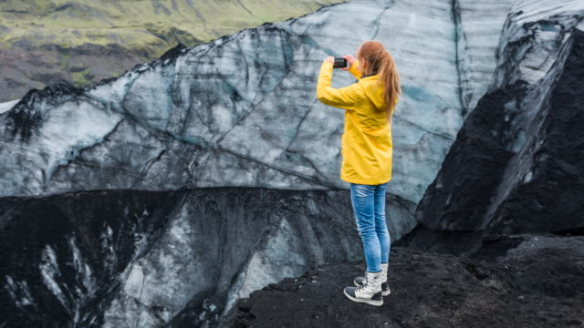 female tourist taking pictures at solheimajokull glacier lagoon in iceland on a rainy day - waterproof clothing stock videos and b-roll footage