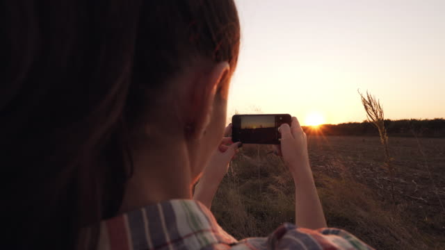 Female tourist taking pictures of the landscape at sunset.