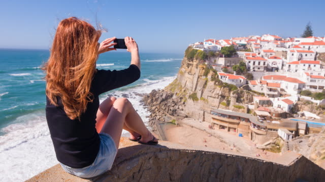 female tourist taking pictures of village on cliffs by ocean - portugal stock videos & royalty-free footage