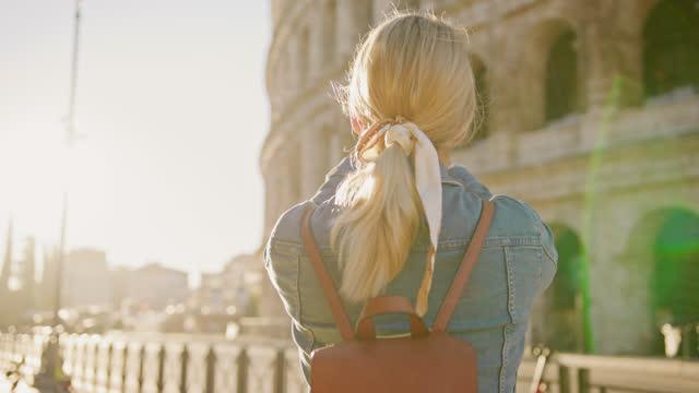 slo mo女性観光客は、彼女がコロッセオに沿って歩いている間、写真を撮るために彼女の携帯電話を使用しています - ラツィオ州点の映像素材/bロール