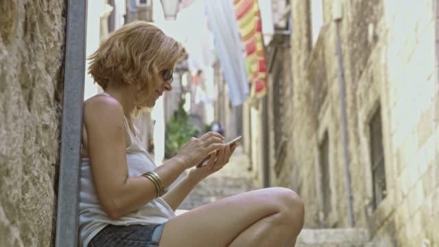 ms-female tourist mit smartphone in gasse - shorts stock-videos und b-roll-filmmaterial