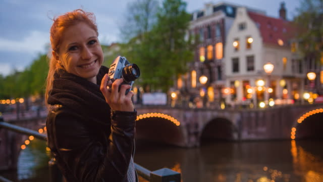 female tourist vacationing in amsterdam, taking pictures of illuminated bridges over canals at night with vintage analog camera, smiling into camera - tourist stock videos & royalty-free footage