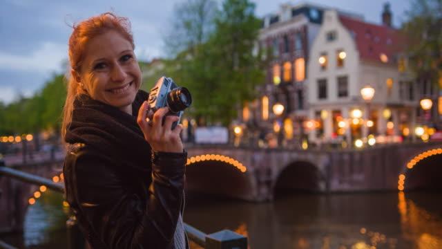 stockvideo's en b-roll-footage met vrouwelijke toerist op vakantie in amsterdam, foto's maken van verlichte bruggen over grachten in de nacht met vintage analoge camera, glimlachend in de camera - tourist