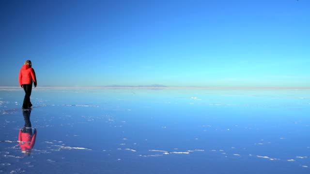 female tourist viewing sunrise on salar de uyuni - ウユニ塩湖点の映像素材/bロール
