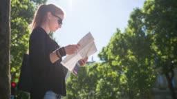 Female tourist with Paris city map admiring national landmarks