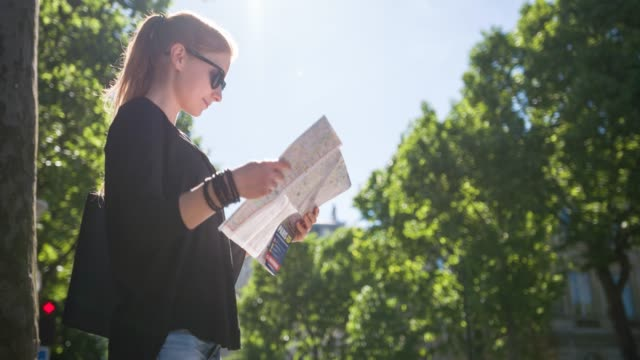 female tourist with paris city map admiring national landmarks - brochure stock videos & royalty-free footage