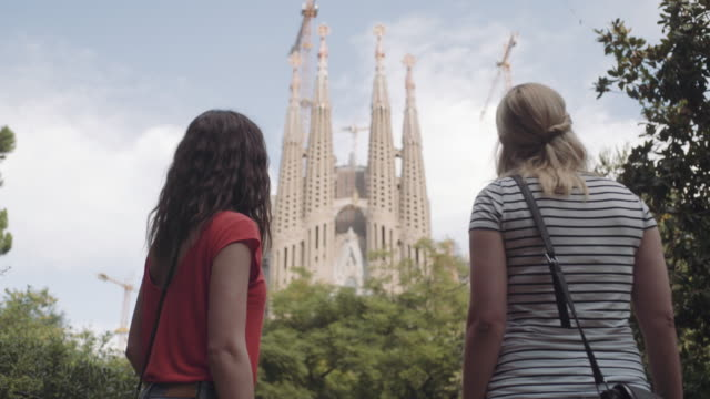 female tourists on vacation photographing cathedral, barcelona - sagrada familia stock videos and b-roll footage