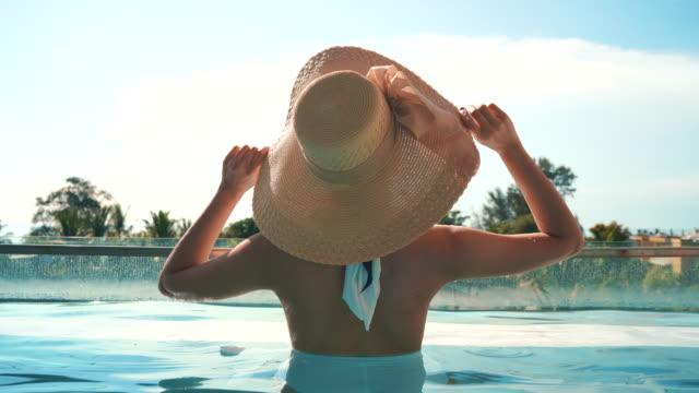 vidéos et rushes de les touristes féminins séjournent dans des chambres de villa de piscine - eau dormante