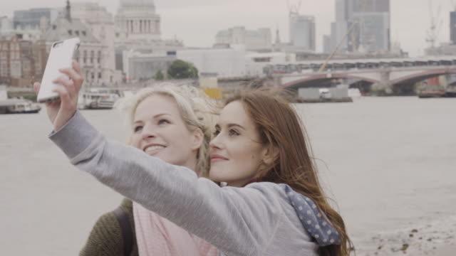 Female tourists taking Selfies at Thames riverside , London.