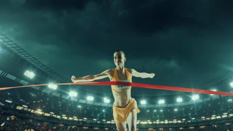 vídeos y material grabado en eventos de stock de femenino de pista y campo runner atraviesa alcanzar la línea de meta - línea de meta