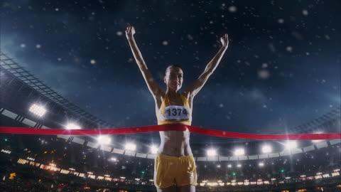 kvinnliga friidrott löparen korsar mållinjen - framgång bildbanksvideor och videomaterial från bakom kulisserna