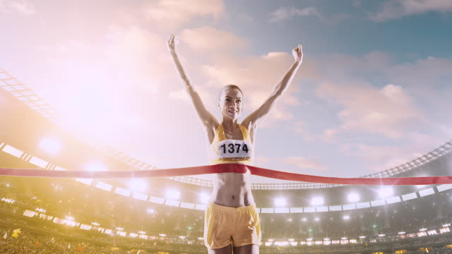 female track and field runner crosses finishing line - linea d'arrivo video stock e b–roll