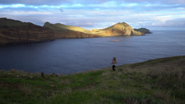 female trail runner ascend mountain, view of cliffs, sunset and peninsula along coastline behind - madeira stock videos and b-roll footage