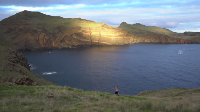 female trail runner ascending hill overlooking madeira coastline - madeira stock videos and b-roll footage