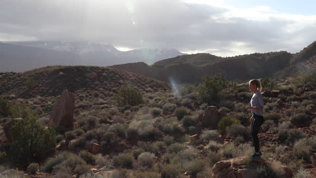 female trail runner ascends desert rock, performs stretches - moab utah stock videos & royalty-free footage