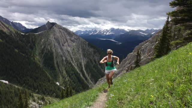female trail runner ascends trail above valley, mountains - mature women stock videos & royalty-free footage