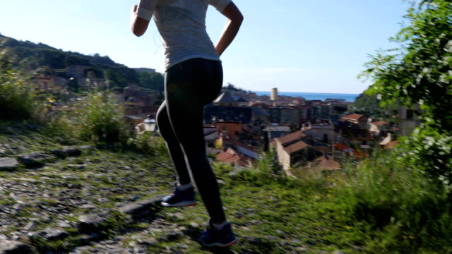 female trail runner jogging up cobblestone path above medieval town - cobblestone stock videos & royalty-free footage