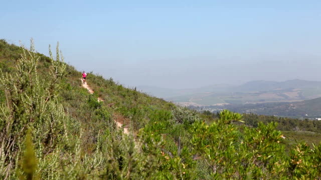 female trail runner runs along a mountain trail above city - cross country running stock videos and b-roll footage