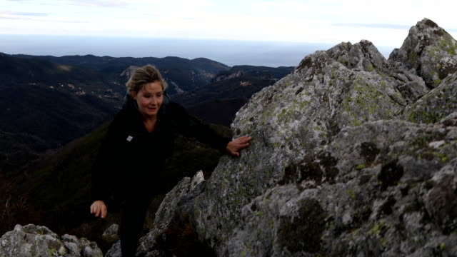 vídeos de stock e filmes b-roll de female trail runner runs along rugged rocky outcrop above seaside hills - resistência