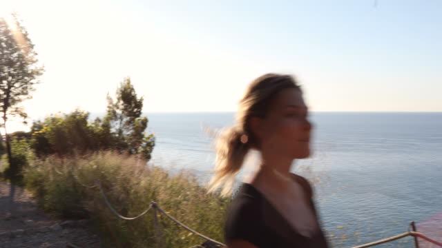 Weiblicher Trailläufer durchquert den Küstenhang bei Sonnenaufgang