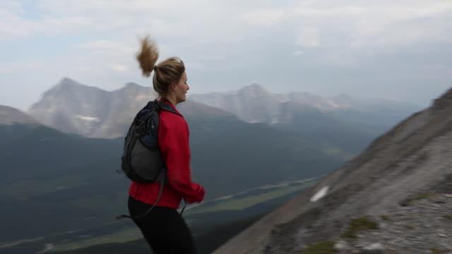 Female trail runner traverses mountain ridge crest