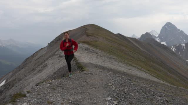 female trail runner traverses mountain ridge crest - coat stock videos & royalty-free footage