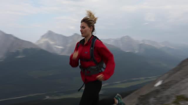 vídeos de stock, filmes e b-roll de female trail runner traverses mountain ridge crest - cabelo louro