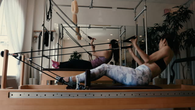 female trainer in fitness studio classroom trains on pilates reformer - only japanese stock videos & royalty-free footage