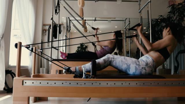 female trainer in fitness studio classroom trains on pilates reformer - リラクゼーション体操点の映像素材/bロール