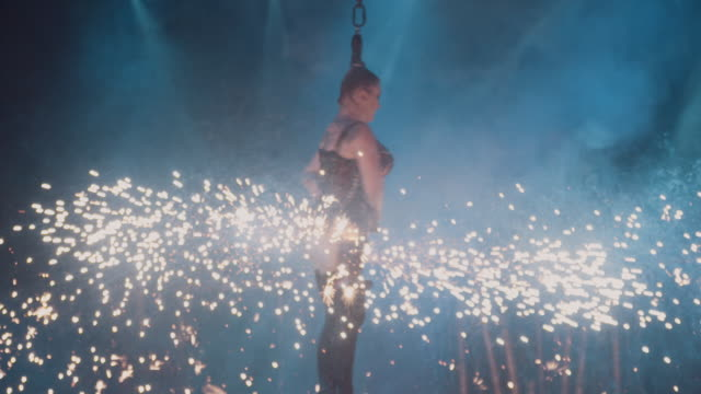 vídeos de stock e filmes b-roll de a female trapeze artist swings across the stage by her hair in slow motion while sparks and pyro effects light up around her - burlesco