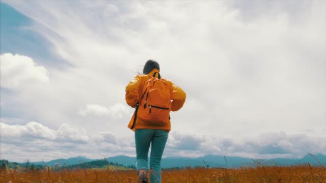 female traveler on mountain hike - raincoat stock videos & royalty-free footage