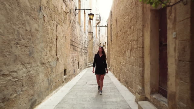 female traveler walking through the narrow street of malta - narrow stock videos & royalty-free footage