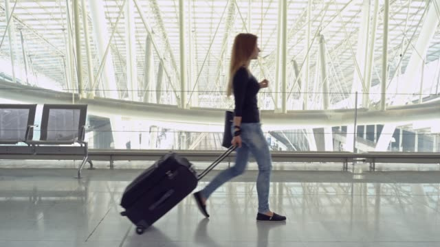 female traveler with luggage walking through airport terminal - wheeled luggage stock videos and b-roll footage