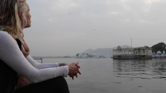 stockvideo's en b-roll-footage met vrouwelijke reiziger pauzeert boven lake en zwevende paleis - one mature woman only