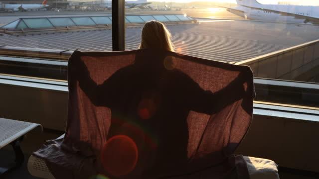 weibliche reisende zieht die decke über schultern, am flughafen - eingewickelt stock-videos und b-roll-filmmaterial