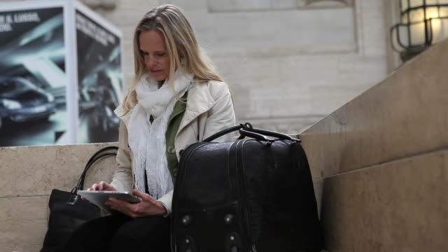 vídeos de stock e filmes b-roll de female traveller relaxes while using digital tablet - fotografia de três quartos