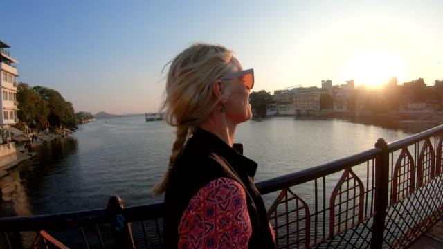 pov weibliche reisende zu fuß über die brücke bei sonnenaufgang - 55 59 jahre stock-videos und b-roll-filmmaterial