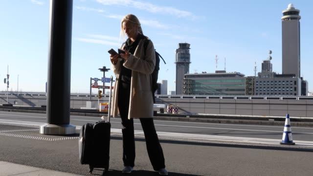 vídeos de stock e filmes b-roll de female traveller walks along corridor outside airport - sinal de estrada