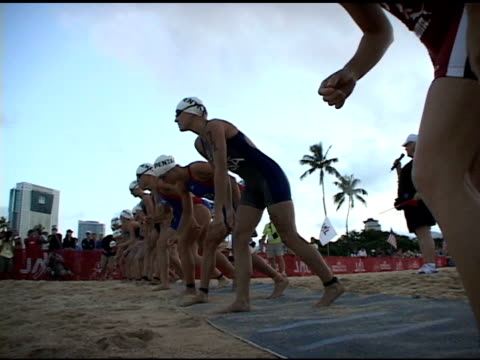 female triathletes enter the water to begin the honolulu triathlon in 2009. female triathletes into water honolulu on january 01, 2010 - triatleta video stock e b–roll