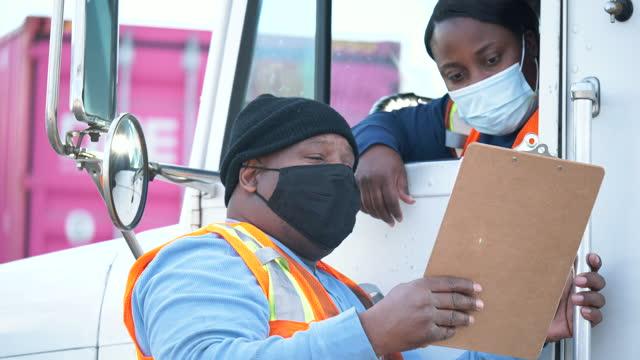 kvinnlig lastbilschaufför, chef med urklipp, ansiktsmasker - standing bildbanksvideor och videomaterial från bakom kulisserna