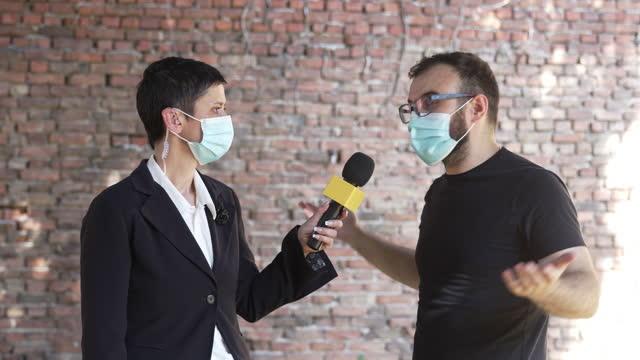 tv-reporterin interviewt einen mann - reporterstil stock-videos und b-roll-filmmaterial
