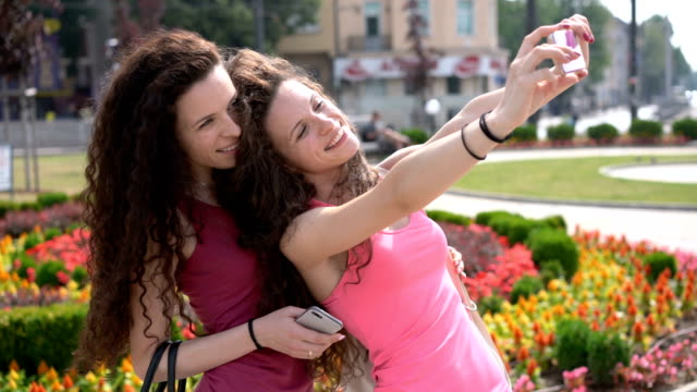 female twins making selfies with the mobile phone - memories stock videos & royalty-free footage