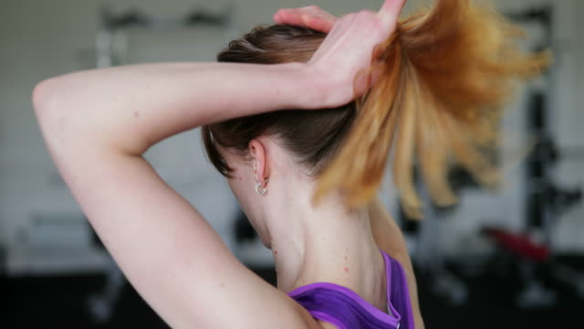 female tying hair up in gym - tie stock videos & royalty-free footage