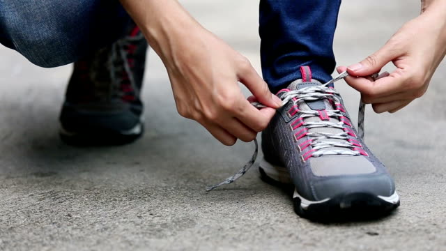 female tying shoelace - shoelace stock videos and b-roll footage