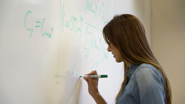 female university student writing a formula on the board with a felt tip marker - blackboard stock videos and b-roll footage