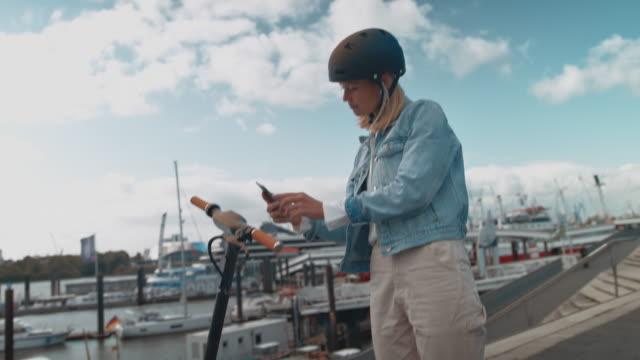 vídeos y material grabado en eventos de stock de scooter eléctrico de desbloqueo femenino con teléfono celular - casco de deportes
